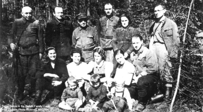 Jewish Holocaust era rescuer Tuvia Bielski and a group of other Jews standing in the woods in an old black and white photo from the Yad Vashem Photo Archives