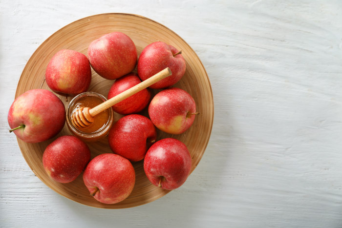 Bowl of apples with a small honey bowl in the center