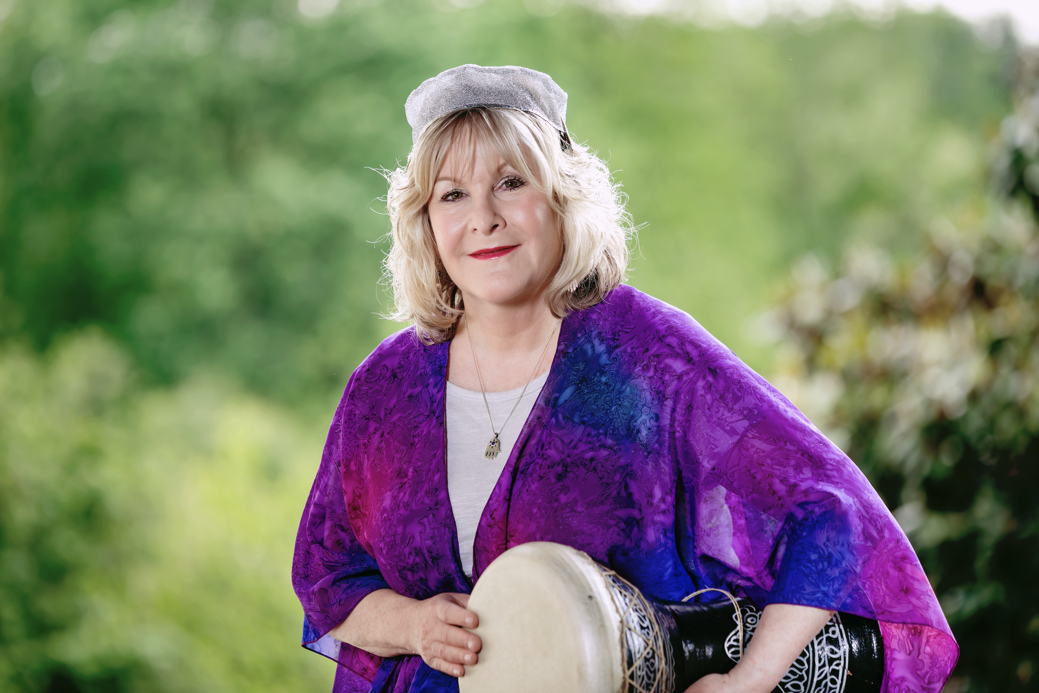 Headshot of Cantor Lisa Levine wearing a blue prayer shawl and holding a small drum