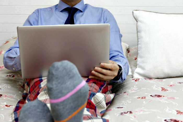 Man holding a laptop in bed while wearing a shirt and tie on top with plaid pajama pants on the bottom