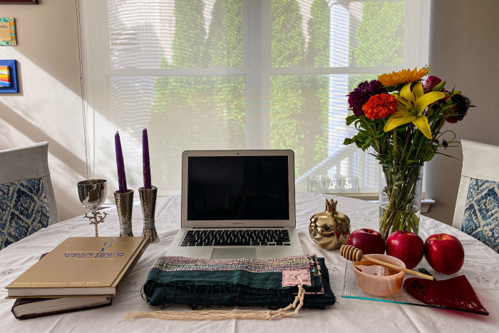 Home sanctuary setup of a table in front of a window bearing a laptop surrounded by flowers and Jewish ritual objects like a prayer book and candlesticks