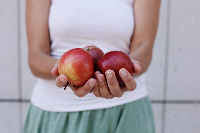 A womans outstretched hands holding three red apples