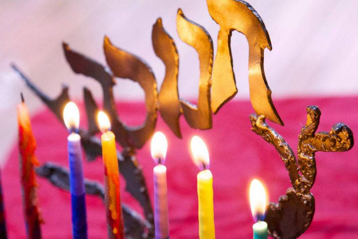 Closeup of six lit candles on a Hanukkah menorah with a pink background