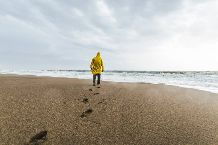 A person in a yellow jacket faces the ocean while standing at the edge of a beach with a line of footprints in the sand
