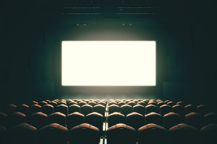 Dark and empty movie theater with a glowing white screen at the front of the room