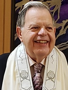 Dr Gary M Levin smiling while wearing a kippah and prayer shawl