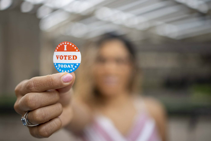 Blurred woman in the background holding to the foreground an I VOTED TODAY sticker