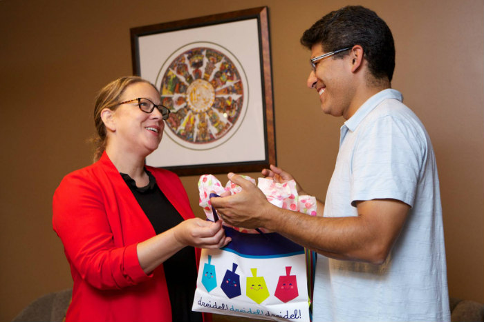 A man and woman exchanging a Hanukkah gift in a bag patterned with colorful dreidels
