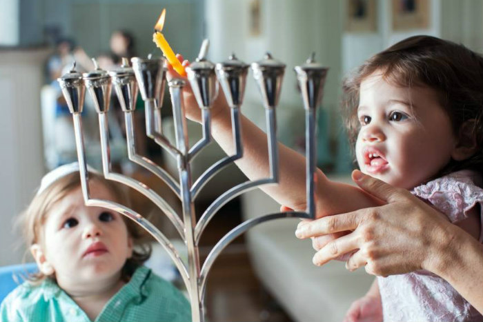 Two young children lighting a silver menorah