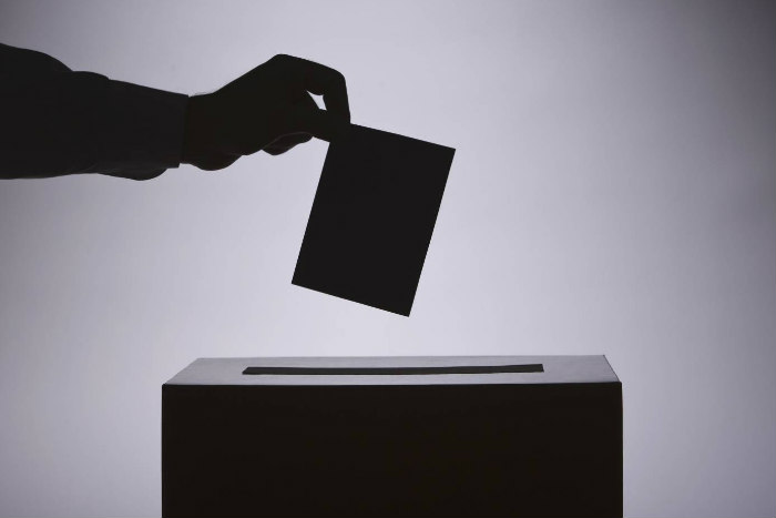 Black and white shadowy image of a hand dropping a ballot into a box
