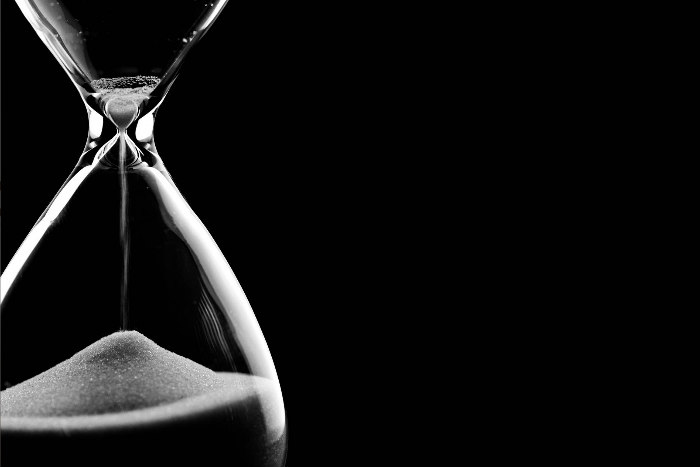 Clear hourglass with white sand against a stark black background