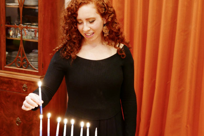 Redheaded young woman lighting a full Hanukkah menorah