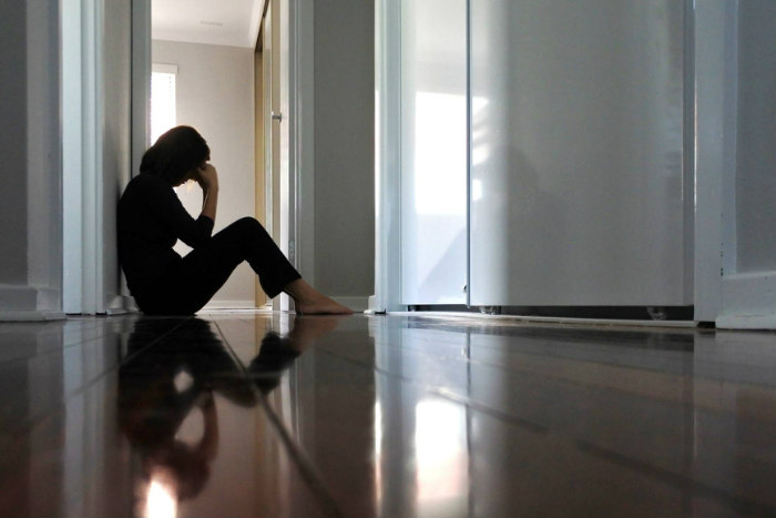 Sad woman sitting on a wooden floor holding her head in her hands as if in grief
