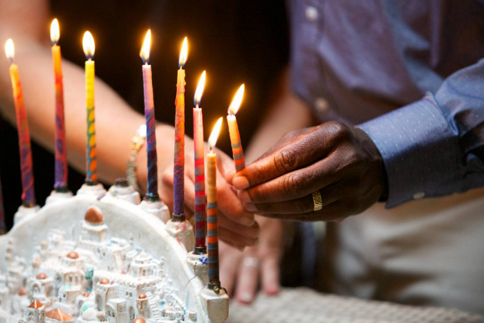 A womans white hand and a mans black hand hold a Hanukkah candle together as they light a Hanukkah menorah