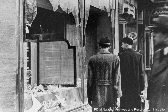 Black and white image of Germans looking at broken storefront windows the day after Kristallnacht