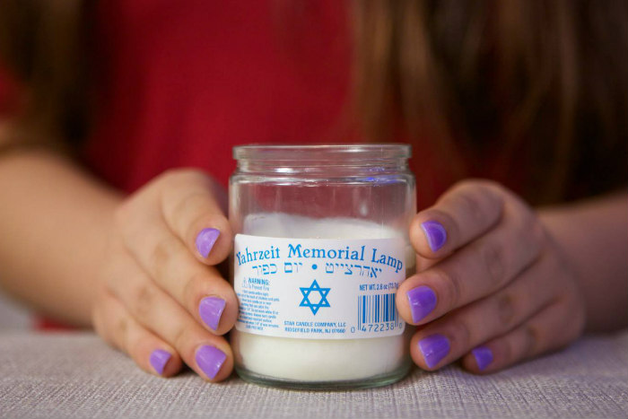 Hands with purple nail polish lightly hold a Yahrzeit candle