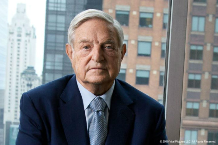 Headshot of George Soros wearing a blazer and blue tie in front of a window with high rise buildings in background