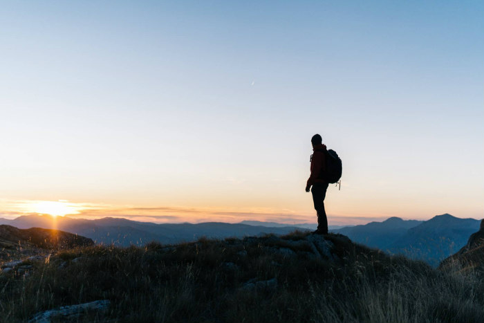 Hiker standing at the top of a peak looking out over nature at sunrise