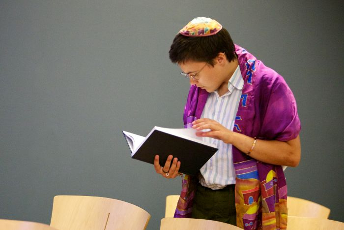 Person wearing a prayer shawl and kippah reading a prayer book in pews alone