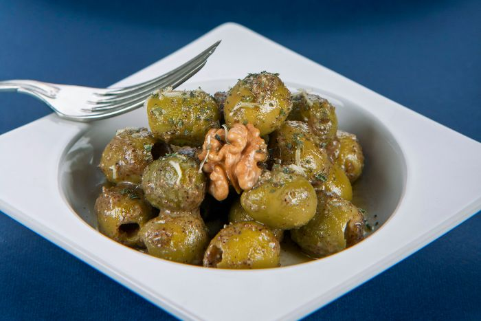 White square bowl containing green olives marinated in herbs with a walnut on top
