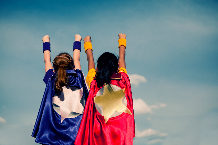Two young girls facing forward wearing superhero capes