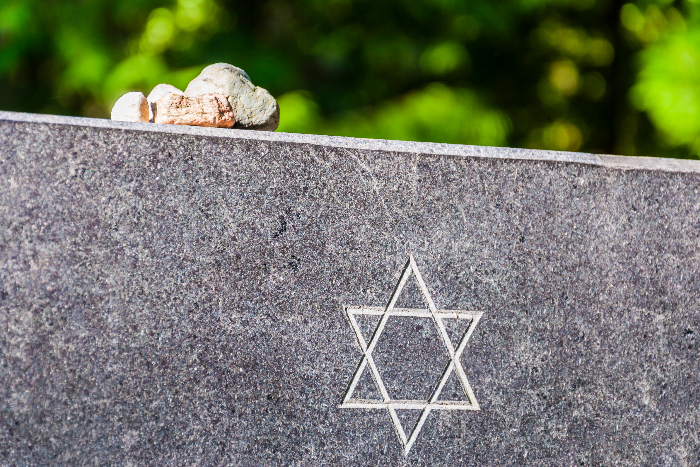 Closeup of a headstone with a Star of David engraving and small stones set on top