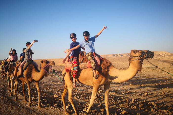 Teens smiling and waving while riding camels in the desert