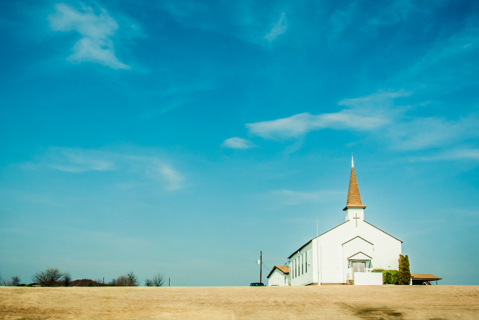 Small white church against a blue sky in a rural area