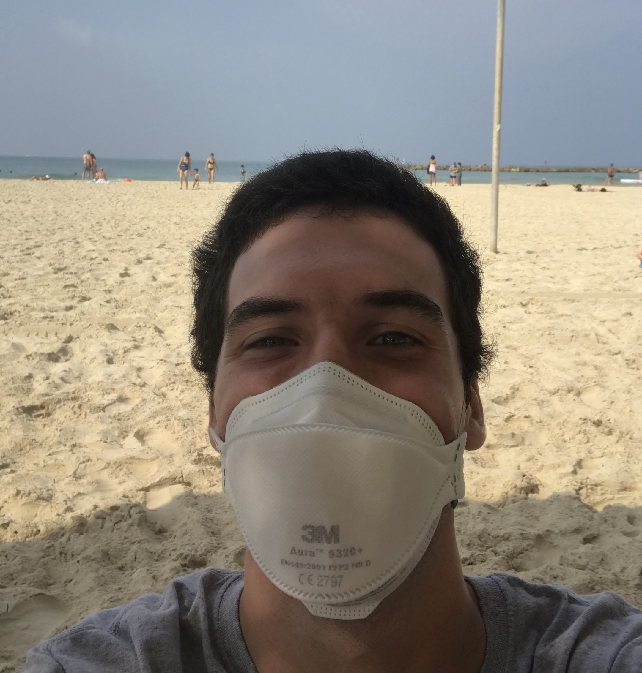 Selfie of Josh Glucksman wearing a face mask on a beach