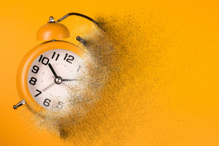 Yellow alarm clock fading away at the edges as if to represent the passage of time