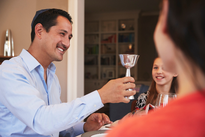 Father holding up a glass of wine at a family seder table
