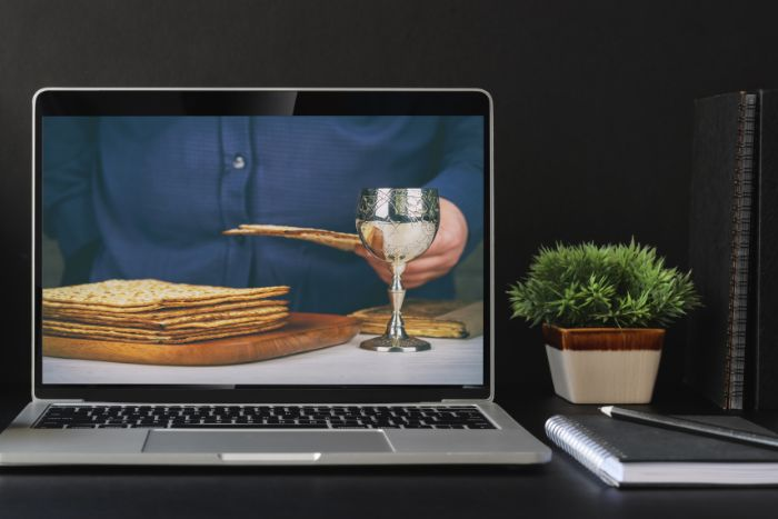 Laptop screen featuring a person sitting in front of a glass of wine and a pile of matzah