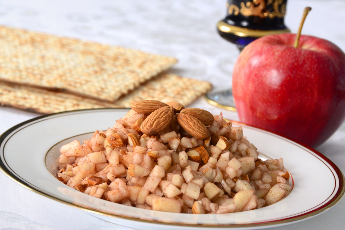 Bowl of charoset with almonds on top and a whole apple in the background