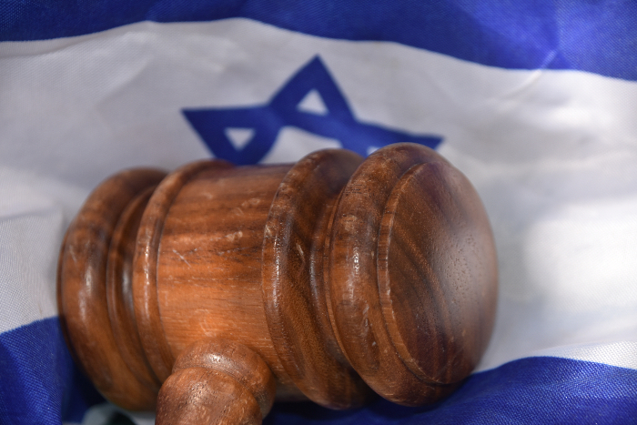Wooden gavel lying on an Israeli flag