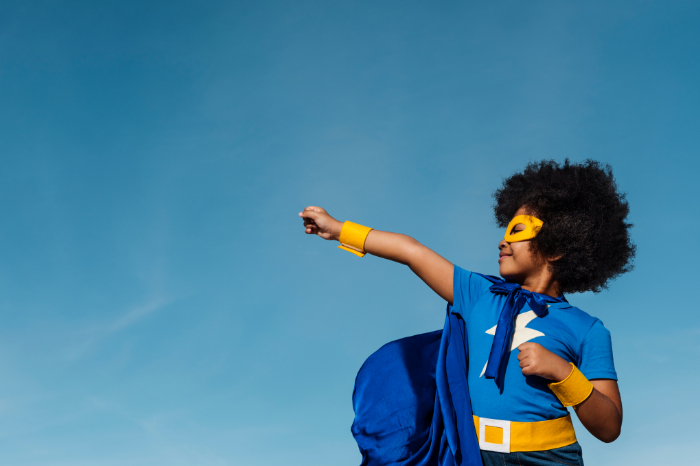 Young boy wearing a superhero costume and punching his arm against the sky