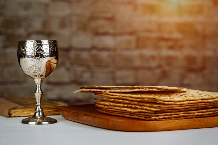 Pile of matzah atop a wooden platter next to a silver Kiddush cup