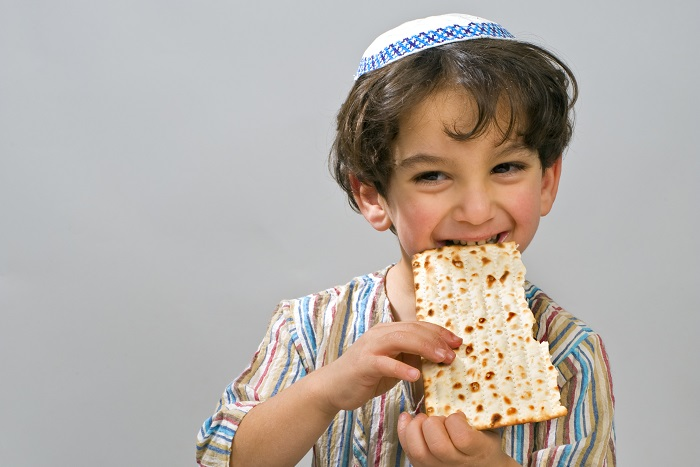 4 year old boy eating a piece of matzah