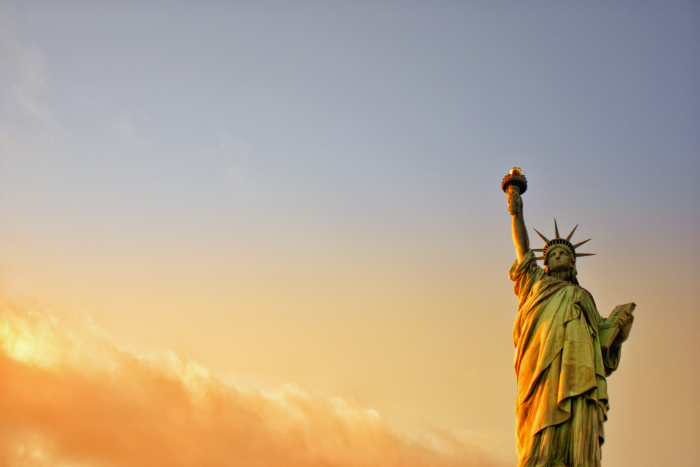 Statue of liberty lit against an orange and yellow sunset