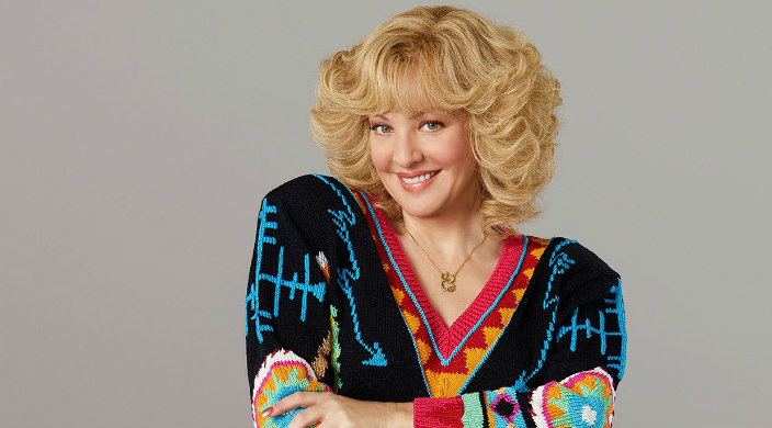 Blond woman from the 1980s with big hair and a colorful sweater with her arms crossed toward the camera