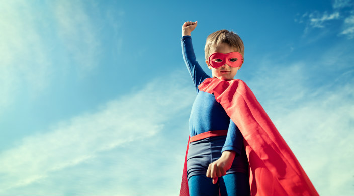 Child in a superhero costume with one fist raised against a blue sky background