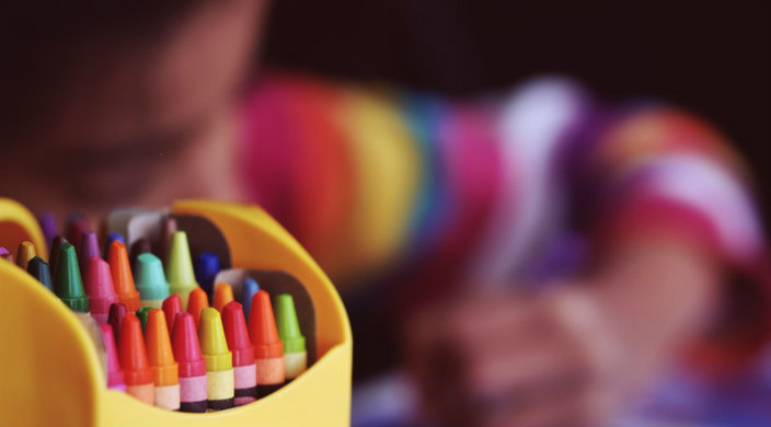 Selective focus with a colorful box of crayons in the foreground and a small child coloring in the background