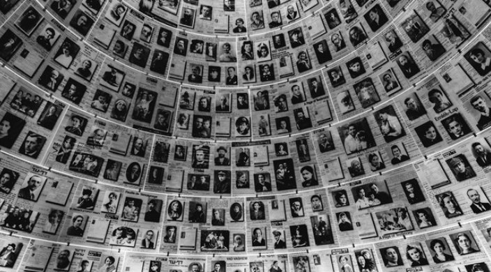 Wall lined with black and white photos of individuals who perished in the Holocaust