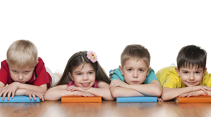 Four young children, each on his/her stomach resting arms on a book