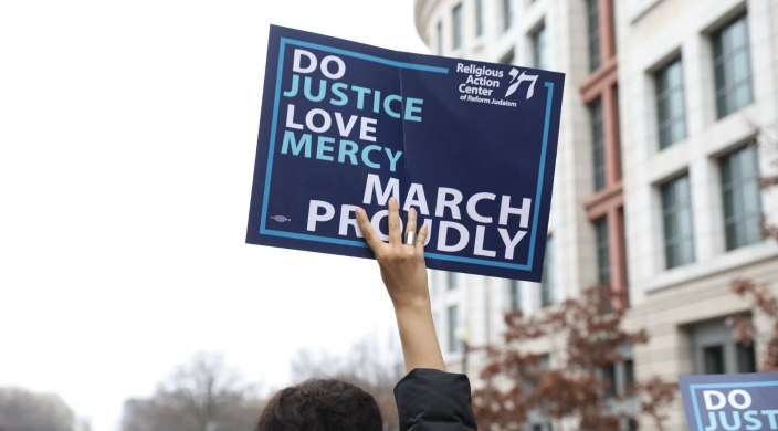 Disembodied hand holding a sign that says DO JUSTICE LOVE MERCY MARCH PROUDLY