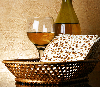 matzah in a basket with glass of wine and a wine bottle