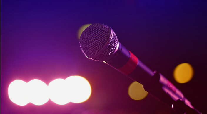 closeup of a microphone with stage lights blurry in the background