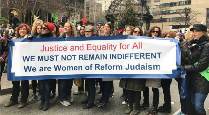 Women march behind a banner that says JUSTICE AND EQUALITTY FOR ALL