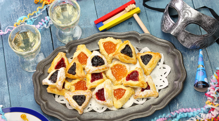 Purim spread featuring hamantaschen party favors and two glasses of white wine