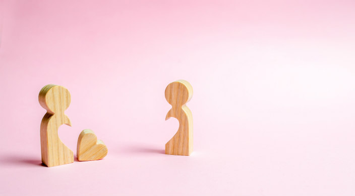 Two person shaped puzzle pieces against a pink background