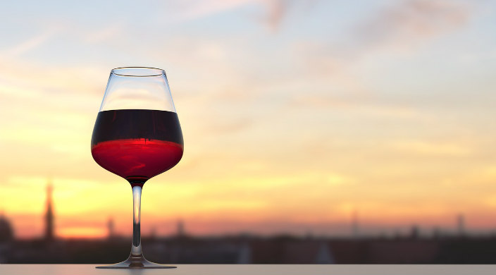 Full glass of red wine sitting on a table in front of a sunset